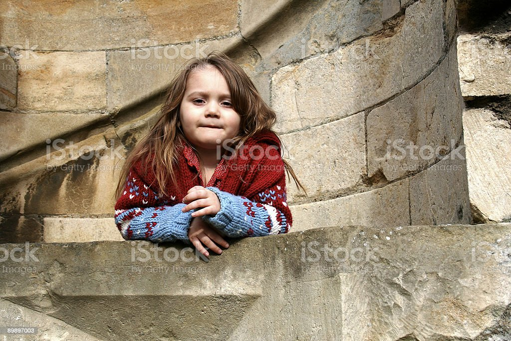 Little girl peering over the wall of an ancient castle royalty-free stock photo
