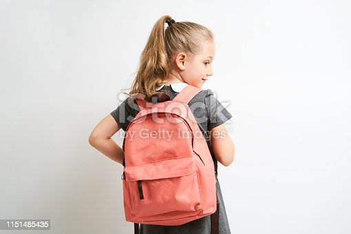 Little girl photographed against white background wearing school uniform dress isolated holding a coral backpack on both shoulders