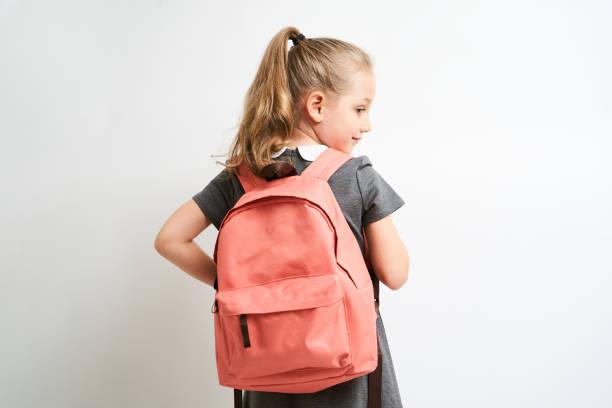 小女孩被拍到在白色背景下穿著校服衣服, 雙肩上都拿著一個珊瑚背包被隔離 - 背囊 個照片及圖片檔