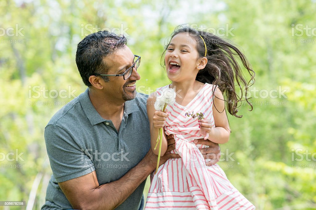 Little Girl Picking Flowers at the Park with Her Dad stock photo