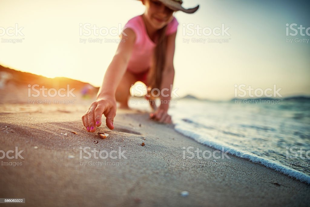 Little girl picking up sea shells at the beach stock photo