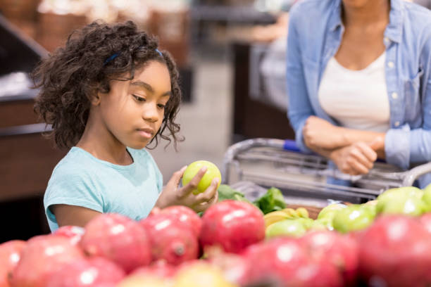 Little girl picks out apples at the grocery store stock photo