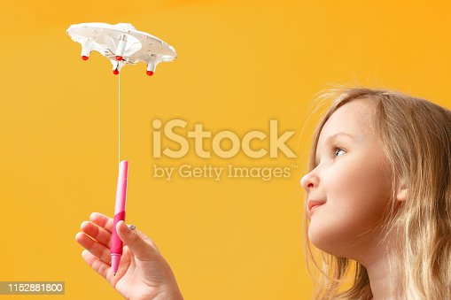 istock A little girl picks up a pen tied to a quadcopter. The concept of delivery, transportation, service, education. 1152881800