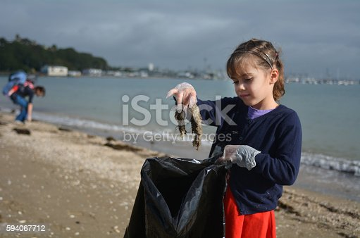 istock Little girl picks up rubbish from the beach 594067712