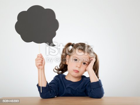 thinking little girl holding blackboard textured speech bubble
