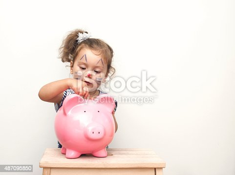 487217358 istock photo Little Girl Placing Coin In Piggy Bank. 487095850