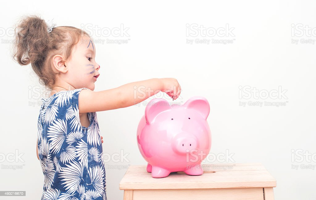 Little Girl Placing Coin In Piggy Bank. stock photo