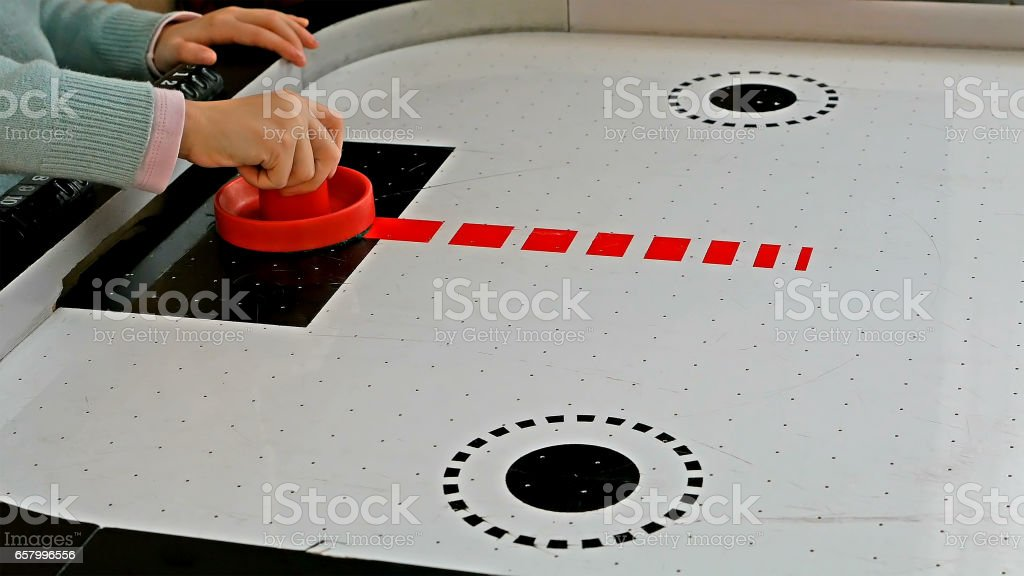 Little girl playing air hockey game stock photo