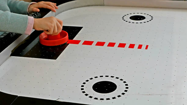 Little girl playing air hockey game - foto de acervo