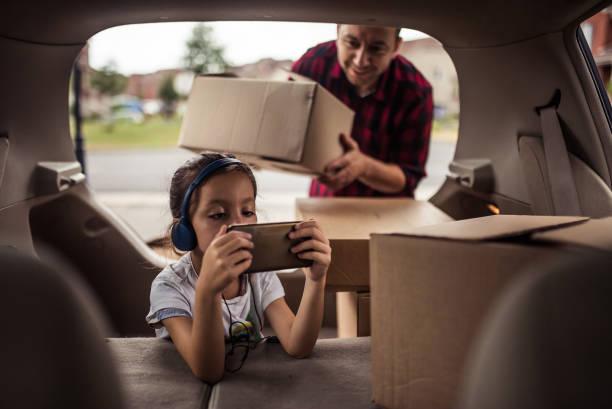 Kleine Mädchen spielen und hören Musik in den Kofferraum des Autos, während ihr Vater Umzugskartons geladen wird – Foto