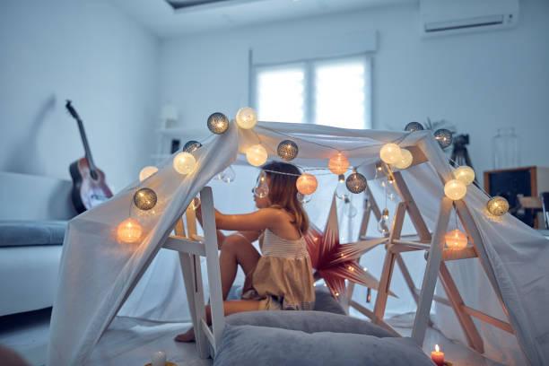 Kleines Mädchen spielen und machen ein Haus Zelt im Raum. – Foto