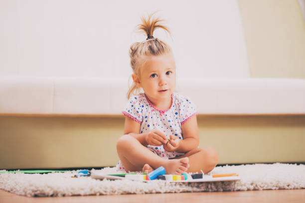 little girl playing at home - sitting on floor stock photos and pictures