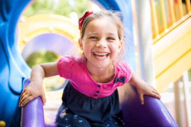 Little Girl Playing At Playground Outdoors In Summer - foto stock