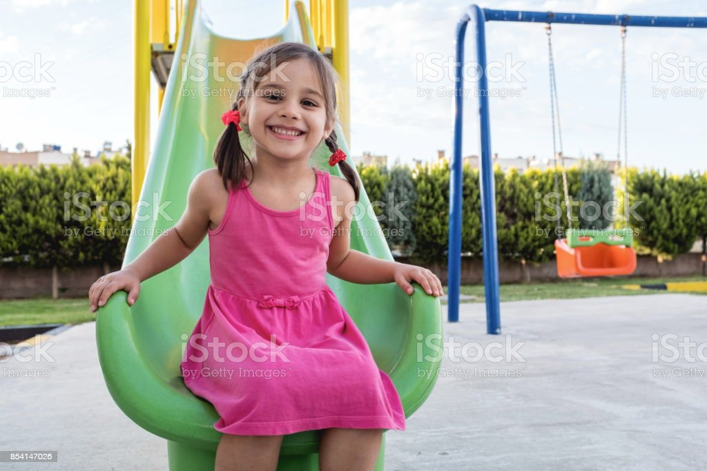 Little Girl Playing At Playground Outdoors In Summer stock photo