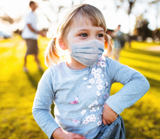 little girl playing at the park with the protective mask stock photo