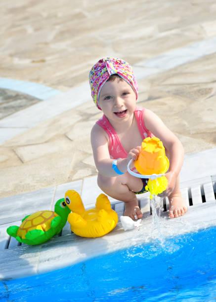 kleine mädchen spielen im pool - armband water stock-fotos und bilder