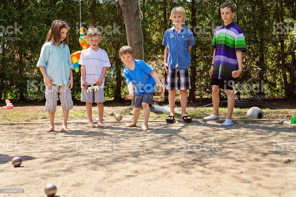 Little girl playing ball game outdoors with boys suburb backyard. stock photo