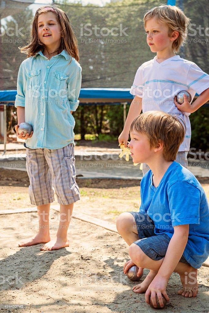 Little girl playing ball game outdoors with boys suburb backyard. stock photo