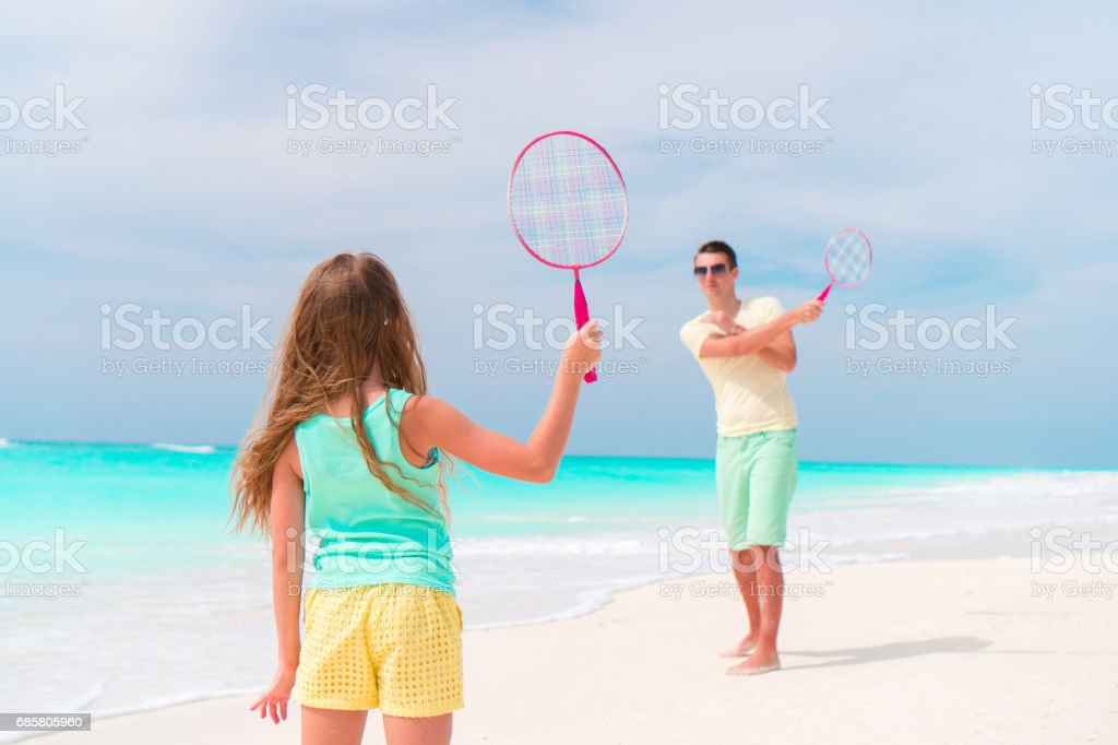 Little girl playing beach tennis on vacation with dad - foto stock