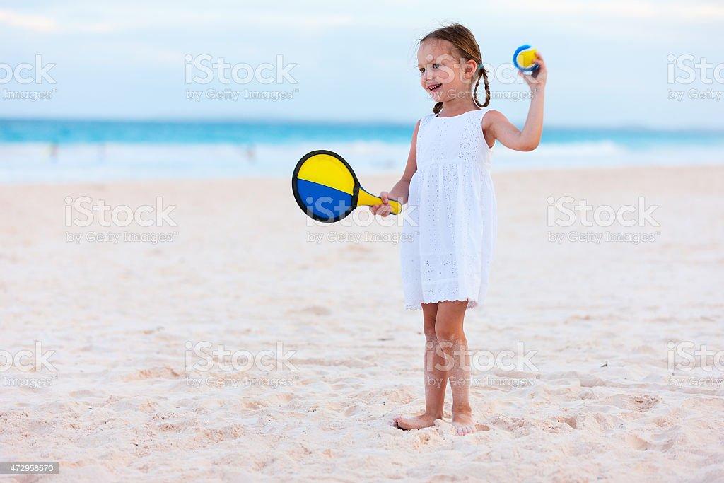 Bambina giocare a tennis sulla spiaggia - foto stock