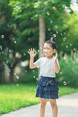 Little girl playing blowing bubbles