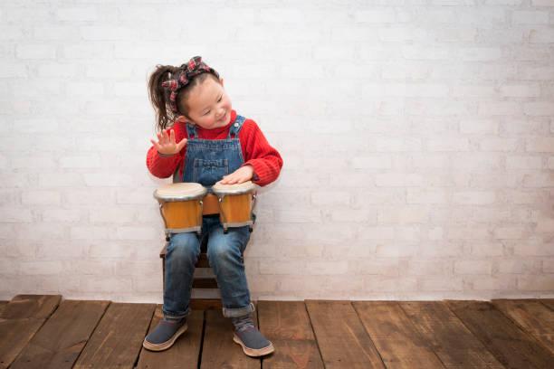Little girl playing bongo stock photo