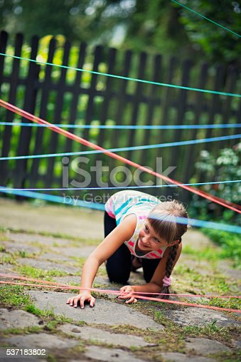 Little girl aged 7 playing burglar trying to avoid detection beams. The beams are made of laundry ropes.