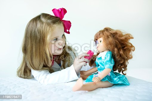 A little girl dressed as a doctor examines her doll.