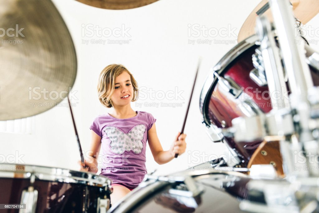 Little girl playing drums stock photo