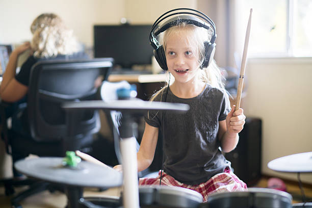 Little girl playing drums when her sister doing homework stock photo