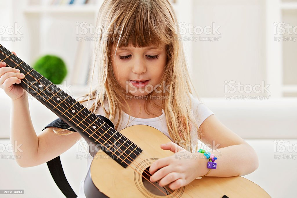 Little girl playing guitar at home stock photo