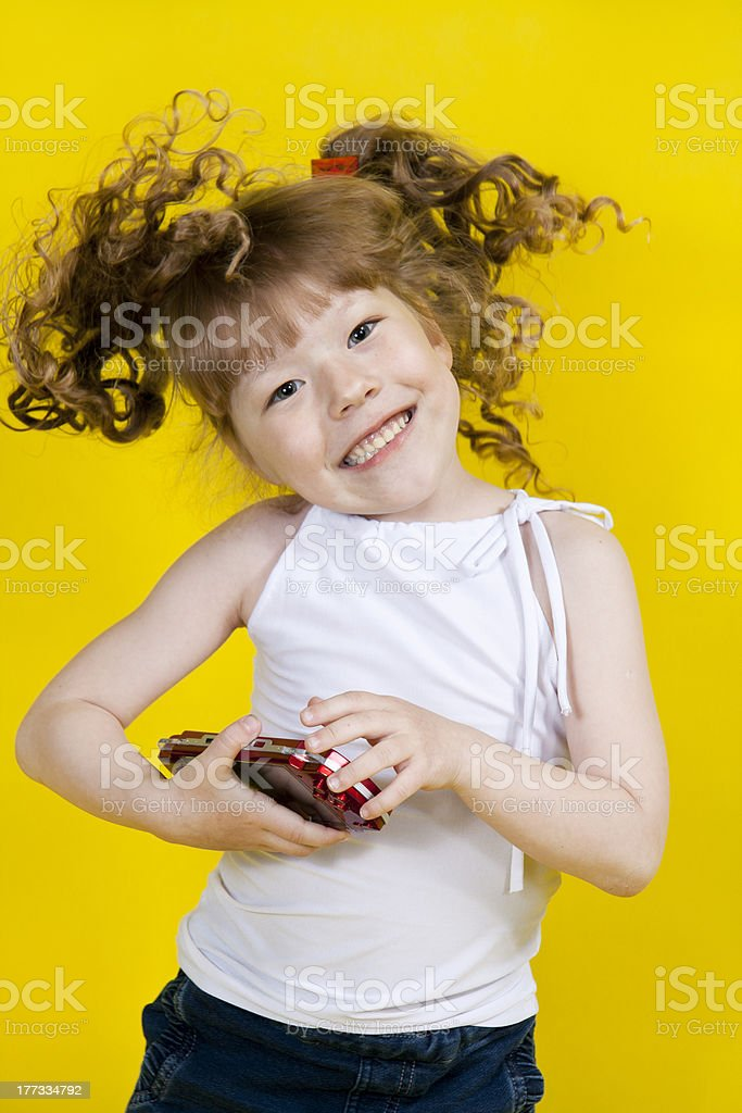 Little girl playing handheld portable game console. Yellow background