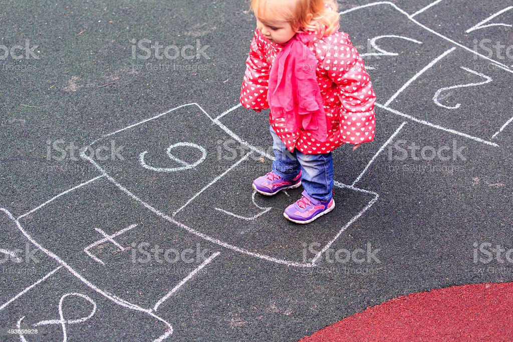 little girl playing hopscotch on playground outdoors stock photo