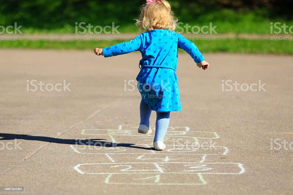 little girl playing hopscotch on playground stock photo