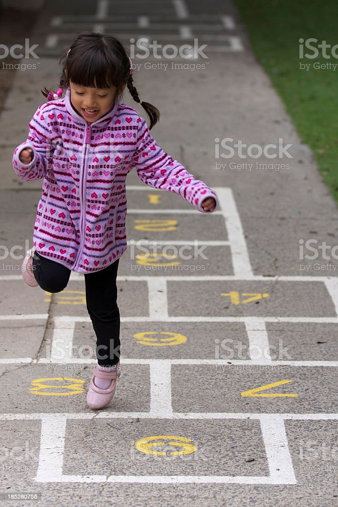 A little girl playing hopscotch stock photo