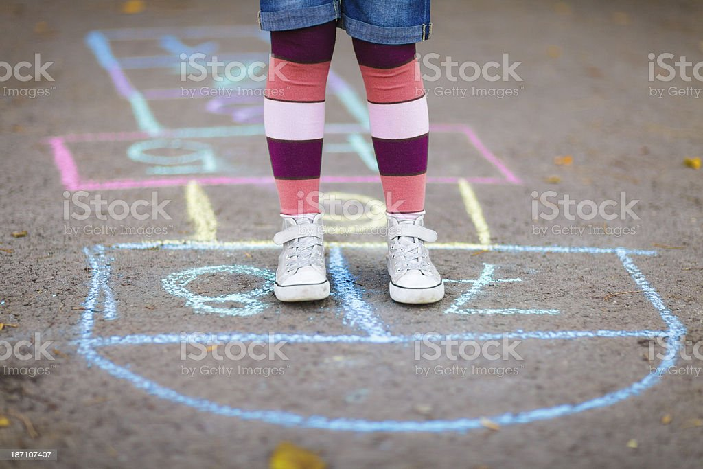 Little girl playing hopscotch stock photo