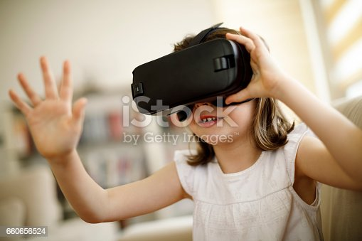 1019302738istockphoto Little girl playing imaginary game with virtual reality headset 660656524