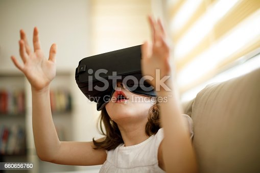 1019302738istockphoto Little girl playing imaginary game with virtual reality headset 660656760
