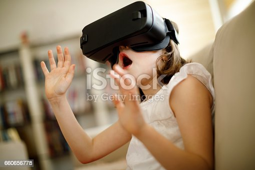 1019302738istockphoto Little girl playing imaginary game with virtual reality headset 660656778