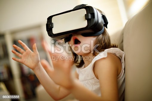 1019302738istockphoto Little girl playing imaginary game with virtual reality headset 660656888