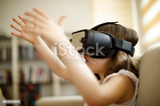 1019302738istockphoto Little girl playing imaginary game with virtual reality headset 660656892