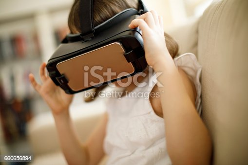 1019302738istockphoto Little girl playing imaginary game with virtual reality headset 660656894
