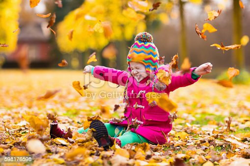 istock Little girl playing in autumn park with golden maple leaves 598176598
