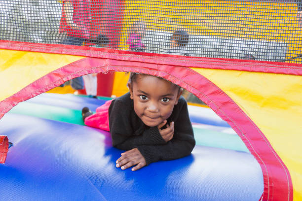 little girl playing in bounce house - school fete stock photos and pictures