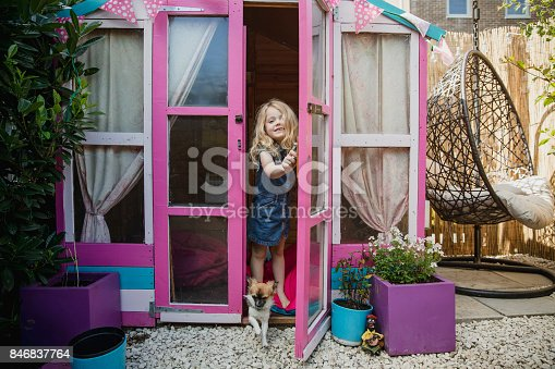 A little girl stands with her pet dog in the doorway of her pink playhouse set in her back garden.
