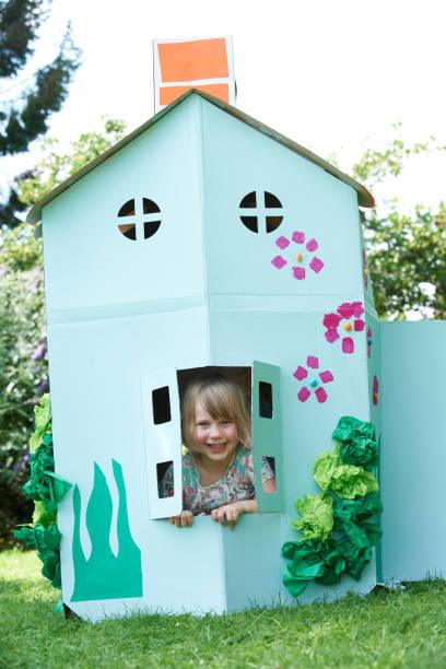 kleine mädchen spielen im haus aus karton - mädchen spielhaus stock-fotos und bilder