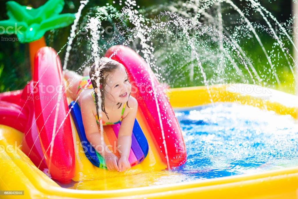 Little girl playing in inflatable garden swimming pool royalty-free stock photo