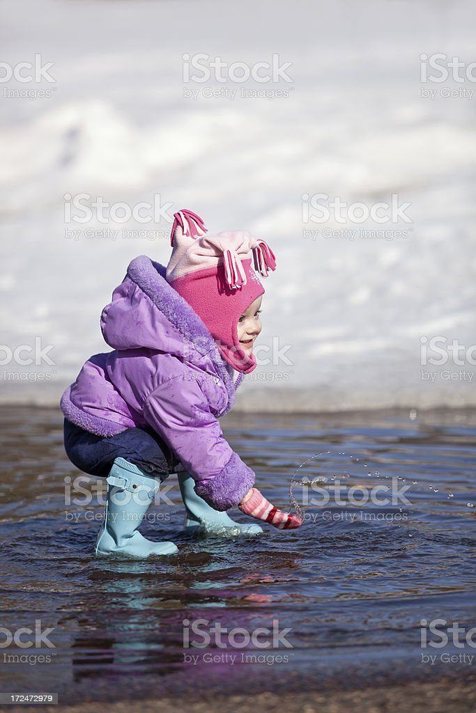 Little Girl Playing in Spring Puddle royalty-free stock photo