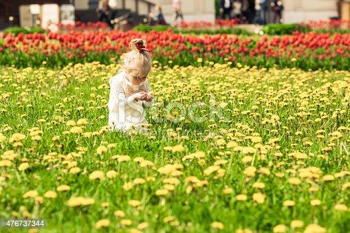 istock Little girl playing in the dandelion field. 476737344