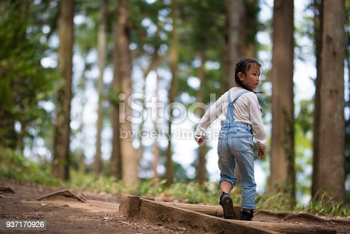 istock Little girl playing in the forest 937170926